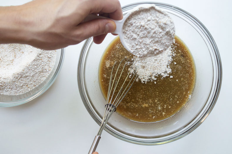 To make Greenlandic cake, for a kaffemik, start by pouring hot water over butter and sugar; mix together and then add your activated yeast and let it sit for 5-10 minutes before you add the sugar