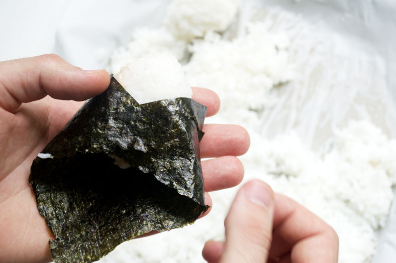 Once you've shaped your onigiri, cut a piece of your roasted seaweed and wrap it around your onigiri. It can be as much seaweed as to cover all the rice, or it can be as little as a strip of seaweed around. It's completely up to you!